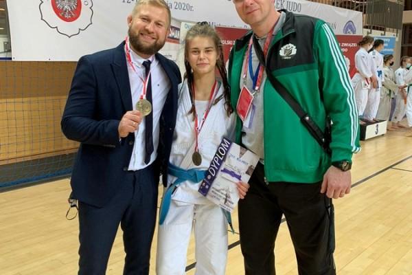 W środku dziewczyna, Mistrzyni Polski w Judo w kimono, w ręce trzyma dyplom. Na szyi zawieszony złoty medal. Z lewej mężczyzna w garniturze. w ręce trzyma złoty medal. Z prawej mężczyzna w dresie.