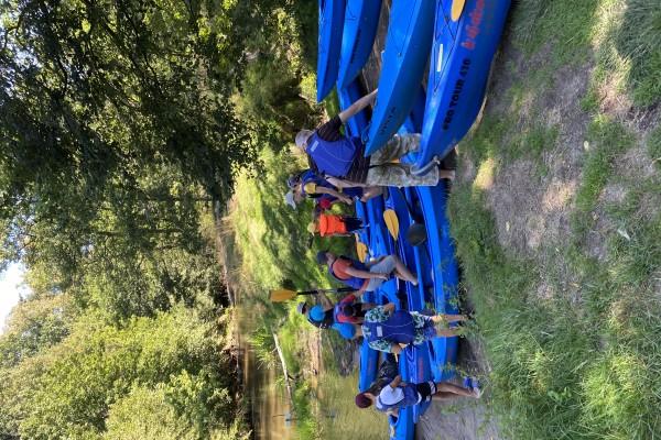 Letnia pogoda. Grupa ludzi  w kapokach przygotowuje się do spływu kajakami.  Kajaki stoją na brzegu. Z lewej strony płynie rzeka.